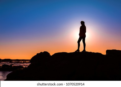 Beautiful woman at the beach on top a of a rock in silhouette