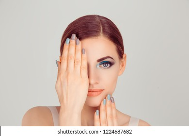 Beautiful woman beauty with artistic blue green eyes makeup holding hands near, covering face showing manicure blue grey nail polish isolated on light gray white background looking at you camera.