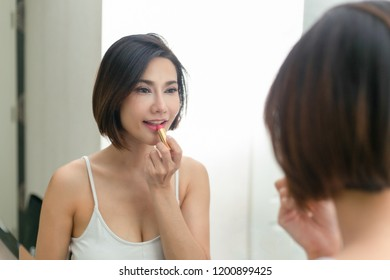 Beautiful woman with beauty face, Lips applying lip balm.