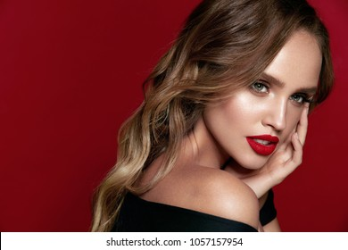 Beautiful Woman With Beauty Makeup On Face, Red Lipstick On Lips And Glamourous Look On Red Background. High Quality Image.