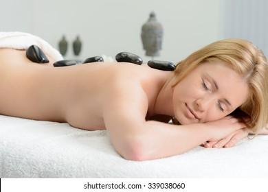 Beautiful woman becoming hot stone massage in spa