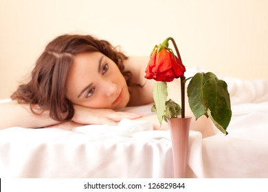 Beautiful woman in bed looking on the rose (focus on rose)