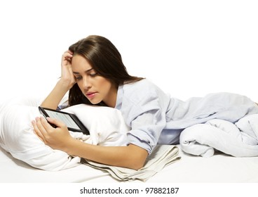 beautiful woman in bed reading ebook on white background