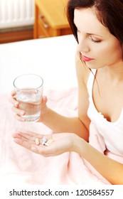 Beautiful woman at bed taking pills.