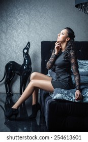 Beautiful woman in the bedroom sitting on the bed and dreaming of his hand to his face. Photo Tinting in cool tones.