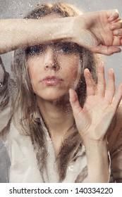 Beautiful woman behind wet glass