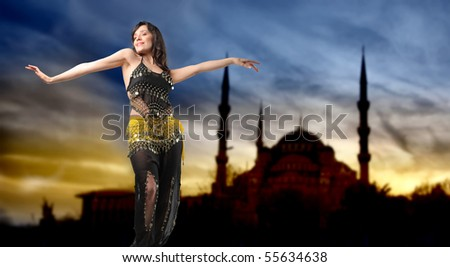 51ea6a3bd Beautiful woman in belly dance clothes with arab mosque on the background
