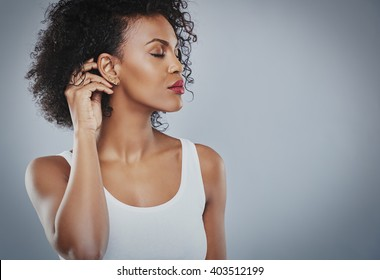 Beautiful woman with big black hair white shirt, Black woman, with closed eyes touching her hair, isolated on grey