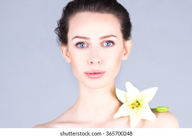 Beautiful woman with big eyes and clear skin. Woman with a flower on the shoulder.
