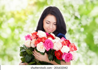 beautiful woman with big roses bouquet smile smell, elegant dress over green tree park outdoor background, concept of 8 march holiday or valentine's day