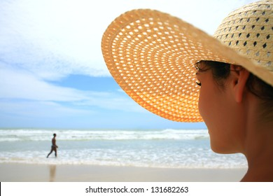 Beautiful woman with big straw hat looking at a man walking on the beach