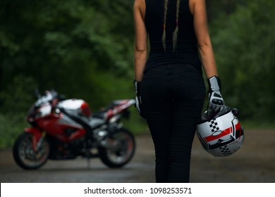 Beautiful woman biker standing on the road with a motorcycle helmet in hand and goes to the superbike