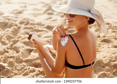Beautiful Woman in Bikini Applying Sun Cream on Tanned  Shoulder. Sun Protection. Skin and Body Care. Girl Using Sunscreen to Skin. Portrait Of Female Holding Suntan Lotion and Moisturizing Sunblock.