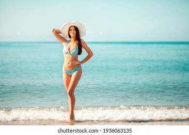 A beautiful woman in a bikini and a beach hat poses standing on the beach. In the background, the sea and sky. Copy space. The concept of beach holidays and summer vacation.