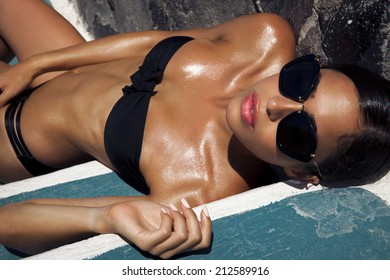 Beautiful woman in bikini and black sunglasses. outdoors shot