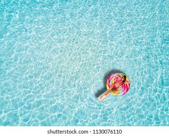 Beautiful woman in a bikini enjoys the tropical sun of the Maldives on a lollipo shaped float over the turquoise colored waters