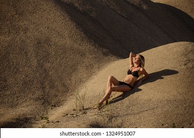 The beautiful woman in bikini on sand