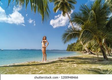 Beautiful woman in bikini on tropical beach. Portrait of happy young woman at sea. Brunette tanned girl in swimwear enjoying and walking on beach.