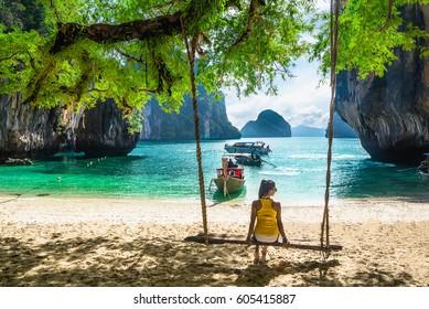 Beautiful woman in bikini relaxing on wooden swing under tree on tropical beach, Koh Lao Lading island, Andaman sea, Krabi province, Thailand