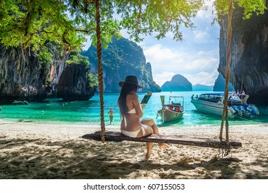 Beautiful woman in bikini relaxing on wooden swing under tree using tablet on tropical beach, Koh Lao Lading island, Andaman sea, Krabi province, Thailand