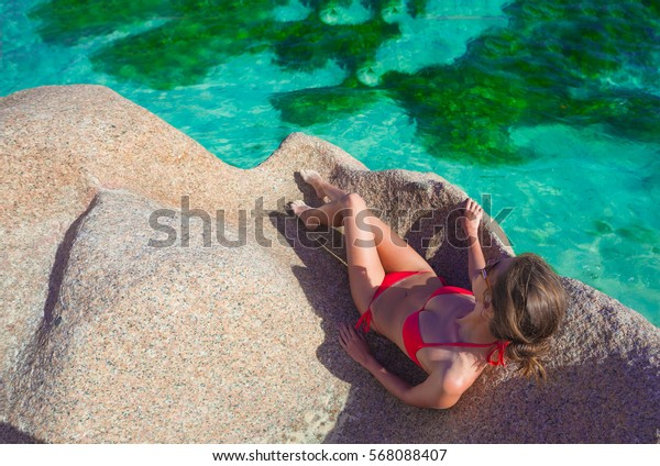 beautiful woman in bikini relaxing on the rocks over the sea. La Digue, Seychelles