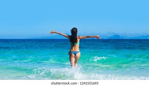Beautiful woman in bikini run into blue tropical sea
