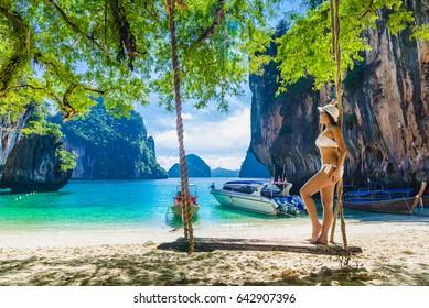 Beautiful woman in bikini standing on wooden swing under tree and looking destinations sea beach, Koh Lading island, Andaman sea, Krabi province, Thailand