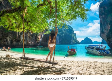 Beautiful woman in bikini standing and relaxing on wooden swing under tree and looking destinations beach, Koh Lao Lading island, Andaman sea, Krabi province, Thailand