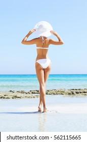Beautiful woman in bikini. Young and sporty girl posing on a beach at summer.