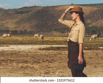 Beautiful woman with binoculars at savanna in Kenya