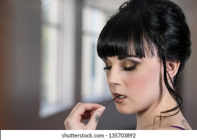 Beautiful woman biting a bobby pin before putting it into her hair