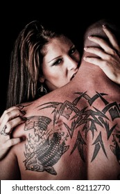 Beautiful Woman biting, hugging and looking over the shoulder of a man with tattoos