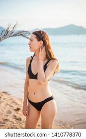 Beautiful woman in black bikini is relaxing on the beach, summer concept