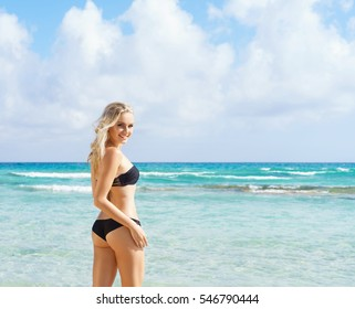 Beautiful woman in black bikini. Young and sporty girl posing on a beach at summer.