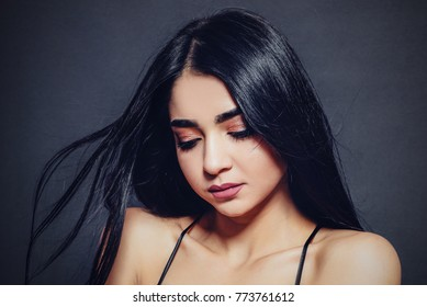 Beautiful woman with black developing straight hair on a dark background. Close-up. Space for text