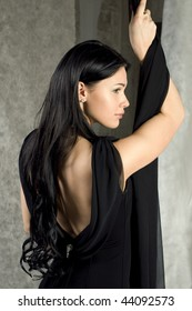 Beautiful woman in a black dress with the bared back