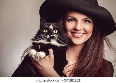 Beautiful woman in black dress and hat with cat