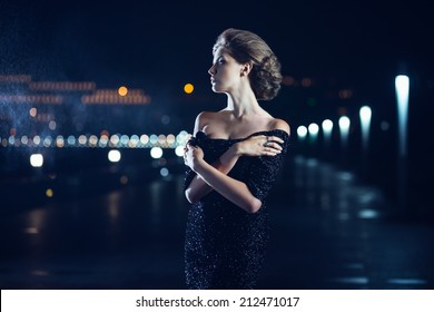 Beautiful woman in black dress posing on a city lights background