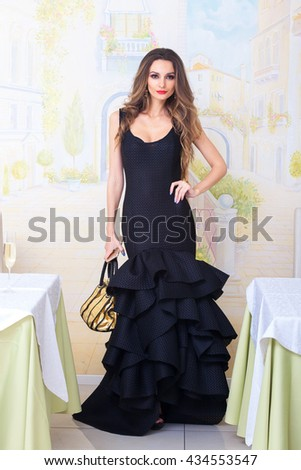 84ea28e2e Beautiful woman in black dress with purse on fashion evening. Posing in the  restaurant near
