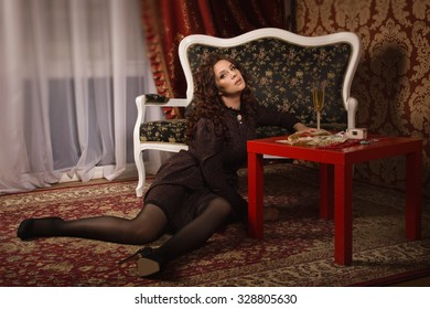 Beautiful woman in a black dress in the vintage interior