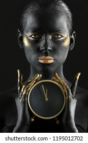 Beautiful woman with black and golden paint on her body holding clock against dark background