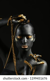 Beautiful woman with black and golden paint on her body holding beads against dark background
