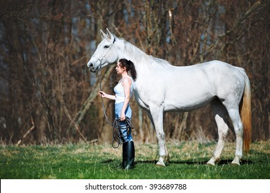 Beautiful woman with black hair stands near a horse and holding her cord. A girl and a white mare standing on a neutral pastel background