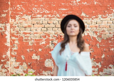 beautiful woman with a black hat posing against the red wall