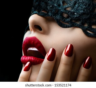 Beautiful Woman with Black Lace mask over her Eyes. Red Sexy Lips and Nails closeup. Open Mouth. Manicure and Makeup. Make up concept. Passion