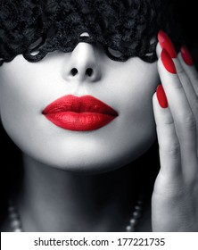 Beautiful Woman with Black Lace mask over her Eyes. Red Sexy Lips and Nails closeup. Sensual Mouth. Manicure and Makeup. Make up concept. Passion. Black and white portrait