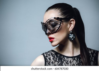 Beautiful Woman with Black Lace mask over her Eyes. Red Sexy Lips and Nails closeup. Open Mouth. Manicure and Makeup. Passion. Beautiful female model posing in carnival mask with bright makeup.