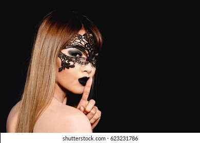 Beautiful Woman with Black Lace mask over her eyes isolated in black background with secret hush pose. Half naked attractive Asian woman with makeup, long brown hair, black eyes, lace erotic mask.