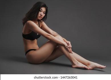 Beautiful woman in black lingerie against dark background
