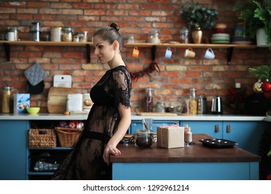 Beautiful woman in black lingerie at the kitchen